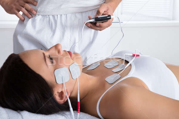 Therapist Giving Electrodes Therapy On Woman's Chest And Face Stock photo © AndreyPopov