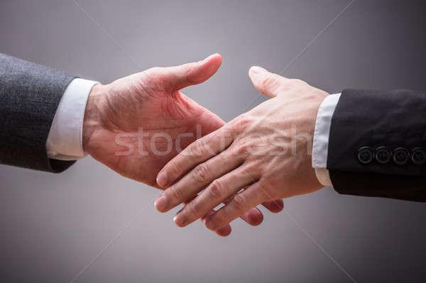 Dos apretón de manos gris mano empresario Foto stock © AndreyPopov