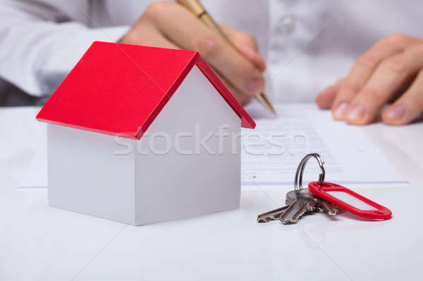 Businessman Calculating House Costs With House Model Stock photo © AndreyPopov