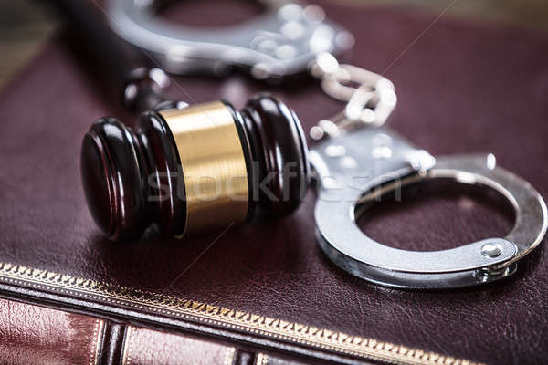 Handcuffs And Gavel On Law Book Stock photo © AndreyPopov