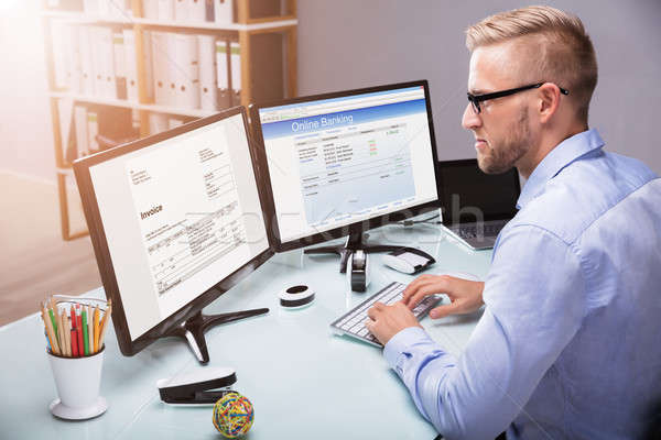 Businessman Doing Online Banking On Computer Stock photo © AndreyPopov