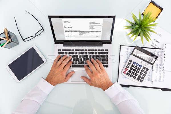 Businessman Analyzing Invoice On Laptop Stock photo © AndreyPopov