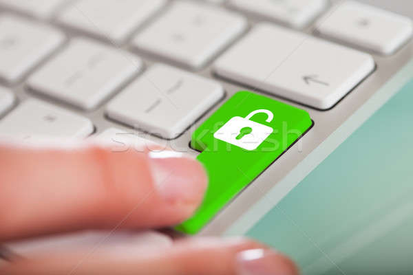 Hand On Open Lock Button Stock photo © AndreyPopov
