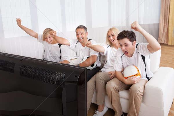 Jubilant family watching television Stock photo © AndreyPopov