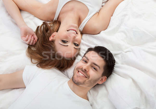 Stock photo: Portrait of happy young couple lying on bed