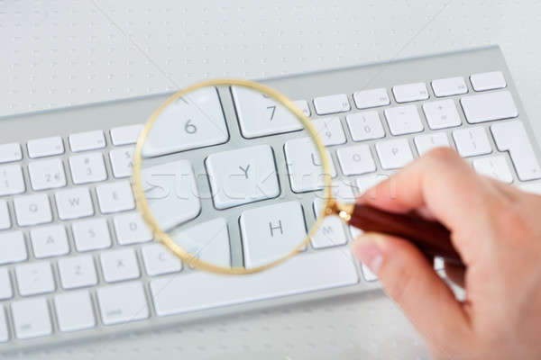 Stock photo: Looking at keyboard key through magnifying glass
