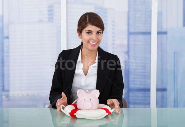 Stock photo: Confident Businesswoman Protecting Piggybank With Lifebuoy