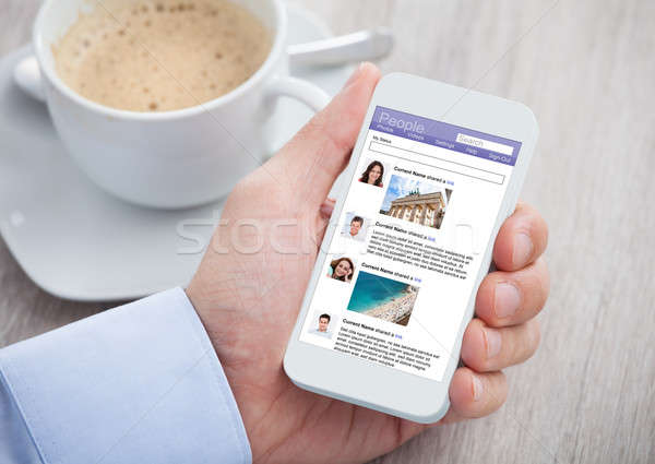 Businessman Surfing Social Networking Site On Mobilephone Stock photo © AndreyPopov