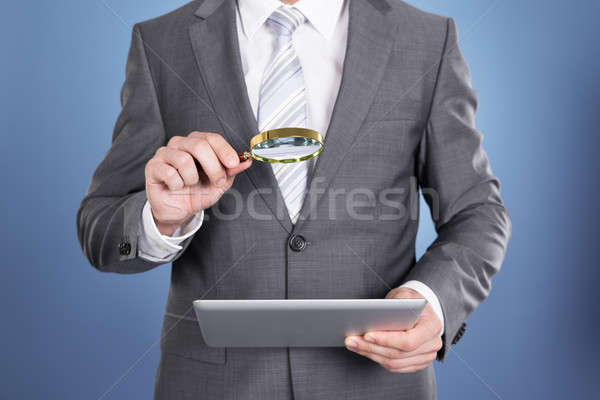 Auditor holding magnifying glass and tablet Stock photo © AndreyPopov