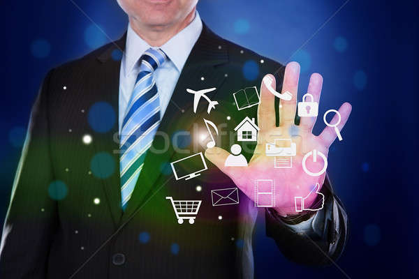Stock photo: Businessman Touching Transparent Screen With Virtual Icons