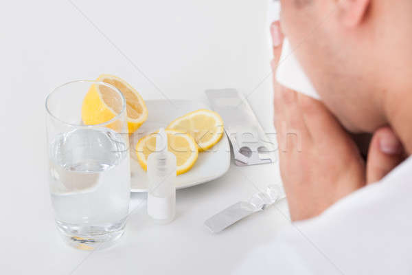 Man suffering from cold with medicines and water glass on table Stock photo © AndreyPopov