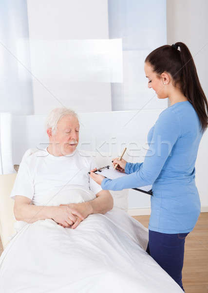 Caretaker With Clipboard Attending Senior Patient Stock photo © AndreyPopov