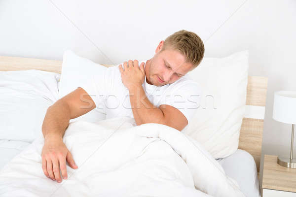 Young Man Suffering From Shoulder Pain Stock photo © AndreyPopov