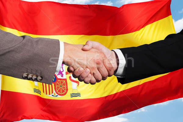 два рукопожатием испанский флаг небе Сток-фото © AndreyPopov