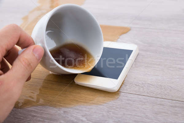 Person's Hand Spilling Coffee On Cellphone Stock photo © AndreyPopov