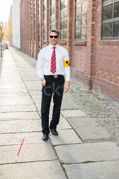 Blind Man Walking On Sidewalk Holding Stick Stock photo © AndreyPopov