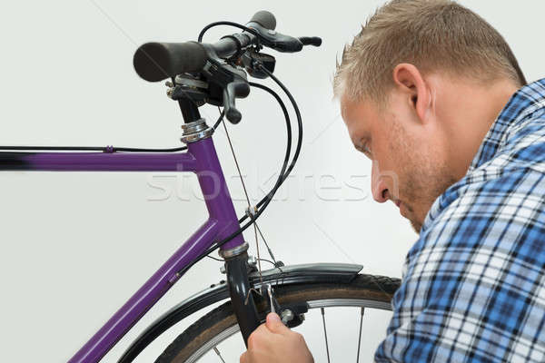 Man Tightening Bolt Of Bicycle Wheel Stock photo © AndreyPopov