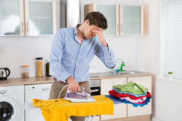 Man Ironing Clothes On Ironing Board Stock photo © AndreyPopov