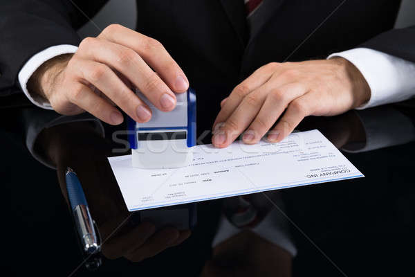 Businessman Stamping Cheque Stock photo © AndreyPopov