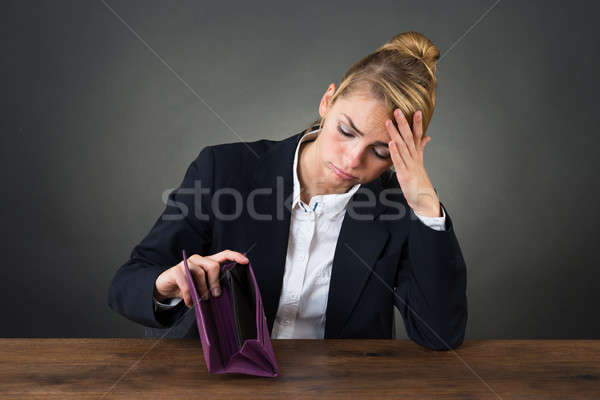 Sad Businesswoman Holding Empty Purse At Desk Stock photo © AndreyPopov