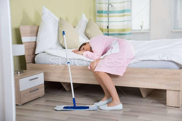 Cansado feminino governanta cama jovem quarto de hotel Foto stock © AndreyPopov