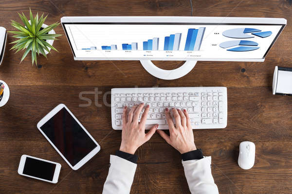 Businessperson Analyzing Graph On Computer Stock photo © AndreyPopov