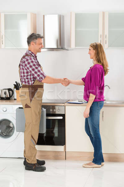 Repairman Shaking Hands With Woman Stock photo © AndreyPopov