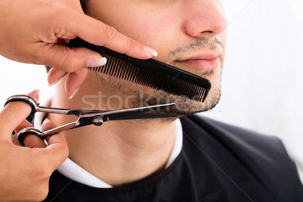 Hairdresser Shaping Man's Beard With Scissor And Comb Stock photo © AndreyPopov