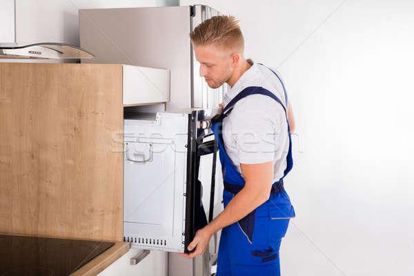 Technician Repairing Oven In Kitchen Stock photo © AndreyPopov