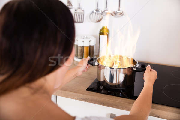 Woman Holding Cooking Pot With Fire Stock photo © AndreyPopov
