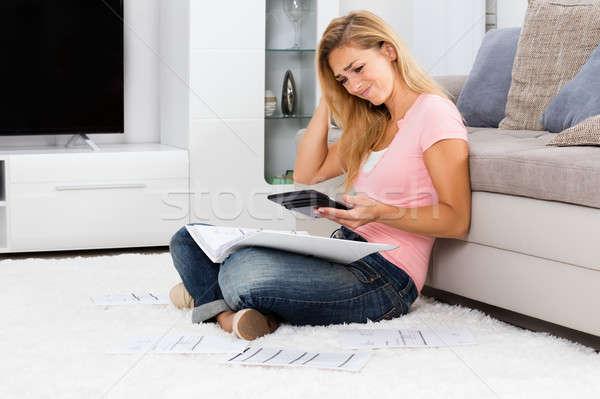 Frustrado mujer mirando calculadora jóvenes papel Foto stock © AndreyPopov