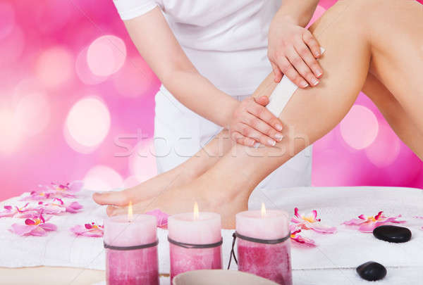 Beautician Waxing Woman Leg With Wax Strip Stock photo © AndreyPopov