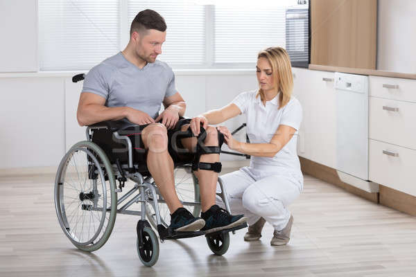 Female Physiotherapist Fixing Knee Braces On Man's Leg Stock photo © AndreyPopov