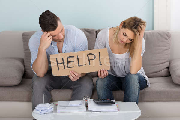 Worried Couple Holding Help Sign While Calculating Bills Stock photo © AndreyPopov
