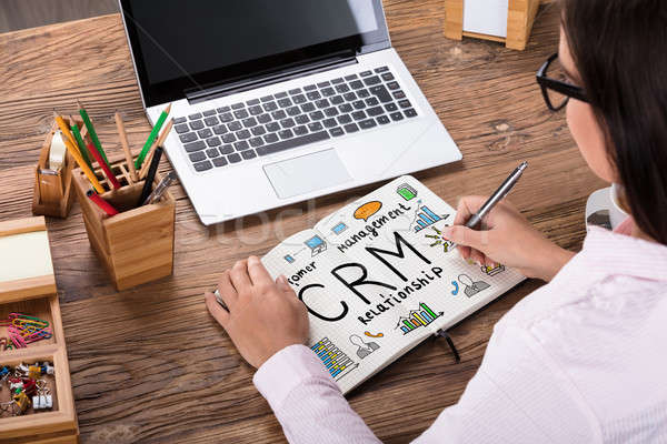 Businesswoman Drawing CRM Plan On Notebook Stock photo © AndreyPopov