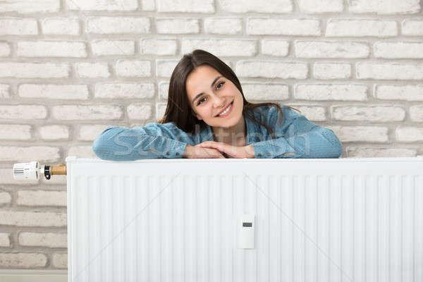Kadın arkasında ısıtma radyatör portre gülümseyen kadın Stok fotoğraf © AndreyPopov
