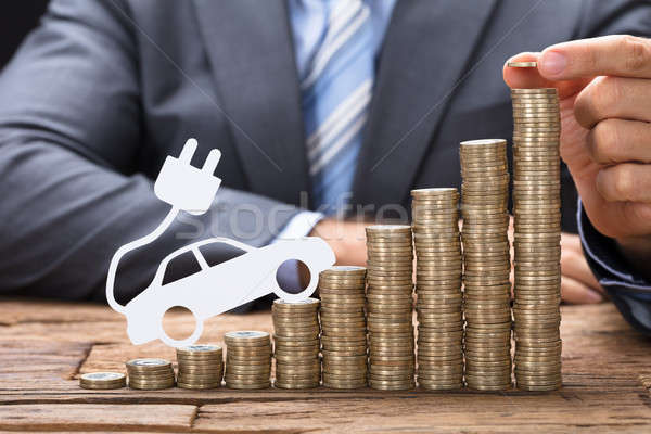 Businessman Stacking Coins With Electric Car At Table Stock photo © AndreyPopov