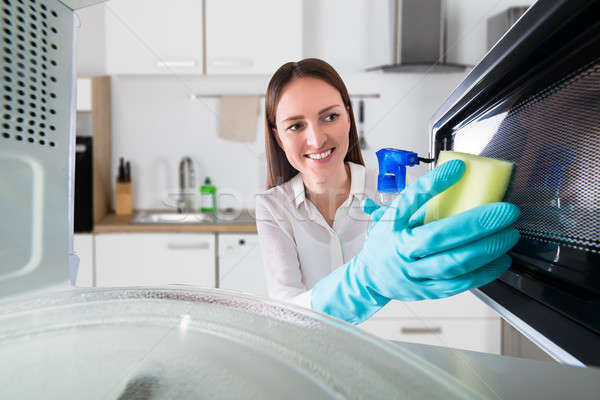 Woman Cleaning Microwave With Spray Bottle And Sponge Stock photo © AndreyPopov