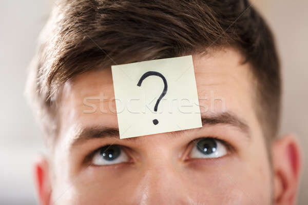 Businessperson's Forehead With Question Mark On Sticky Note Stock photo © AndreyPopov