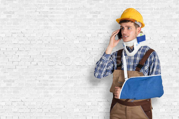 Handyman With Fractured Hand Calling On Mobile Phone Stock photo © AndreyPopov