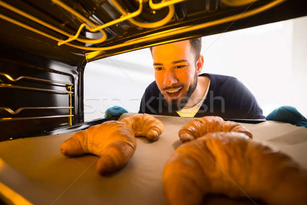 Man Taking Out Tray Of Croissants From Oven Stock photo © AndreyPopov