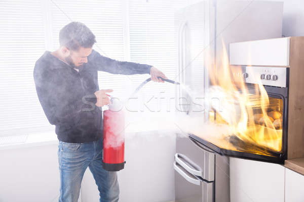 Stock photo: Man Using Fire Extinguisher To Stop Fire Coming From Oven