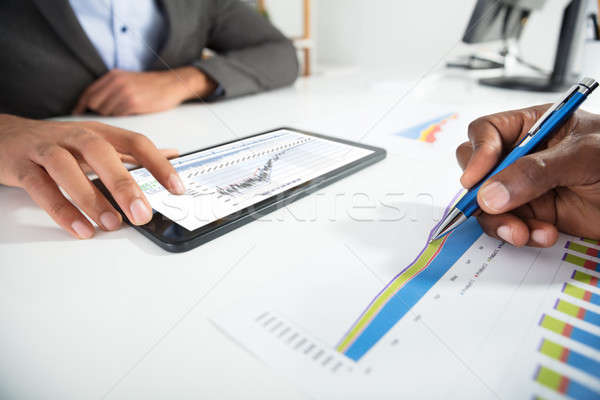 Stock photo: Two Businesspeople Analyzing Graph In Office
