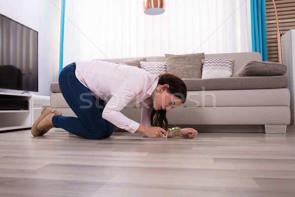 Woman Looking At Hardwood Floor Through Magnifying Glass Stock photo © AndreyPopov