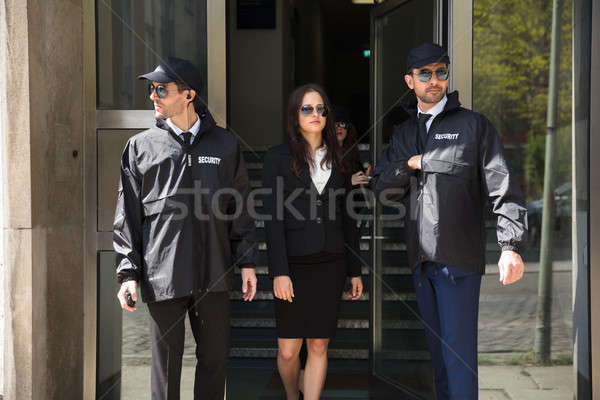 Businesswoman Stepping Out From Office Building Stock photo © AndreyPopov