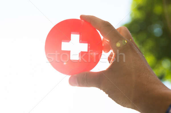 Man holding first aid medical sign Stock photo © AndreyPopov