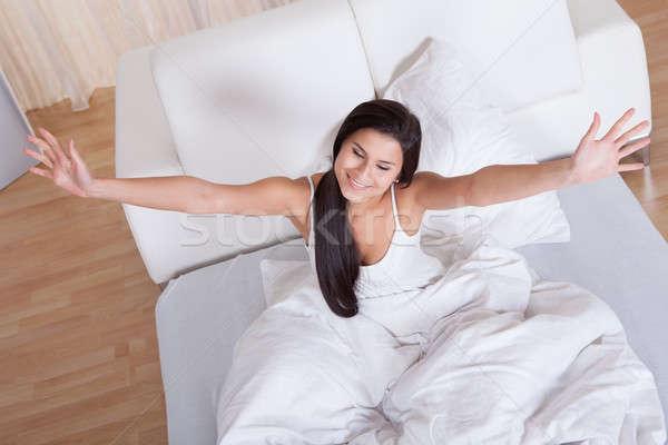 Pretty woman snuggling down in bed Stock photo © AndreyPopov