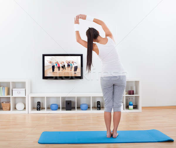 Woman practicing yoga at home Stock photo © AndreyPopov