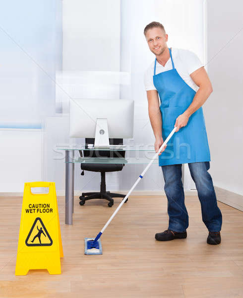 Warning notice as a janitor mops the floor Stock photo © AndreyPopov