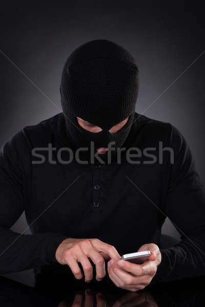 Thief trying to access a stolen mobile phone Stock photo © AndreyPopov